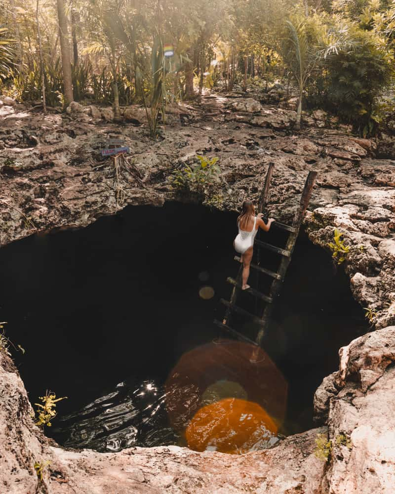 girl stepping into cenote