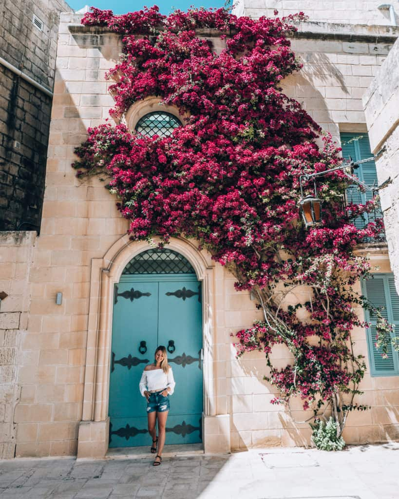girl in doorway surrounded by flowers