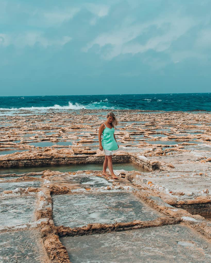 girl standing amongst Gozo salt pan, what to see in Malta