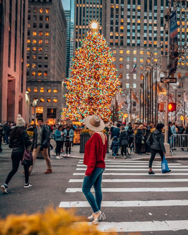 girl wearing red standing in front of a Christmas tree