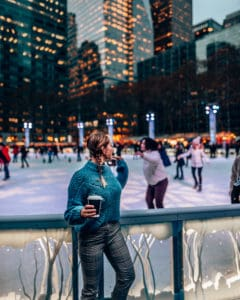 girl standing with hot chocolate standing in front of an ice skating rink