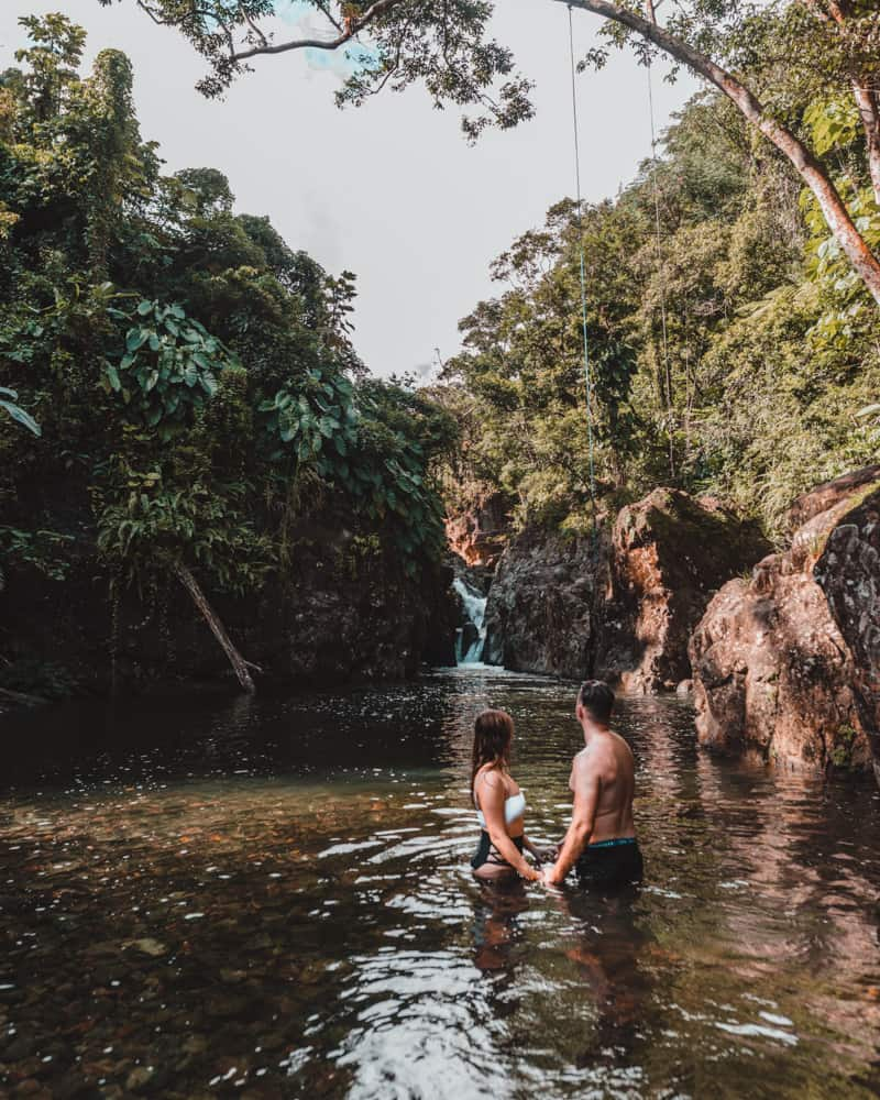 couple standing in lagoon in rainforest