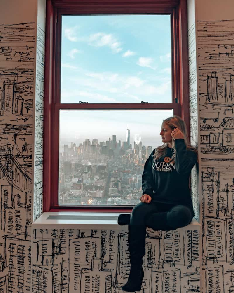 girl sitting in window with view of a city