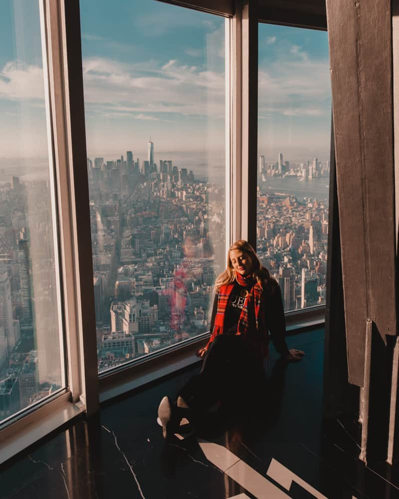 girl sitting in top floor of building with a view