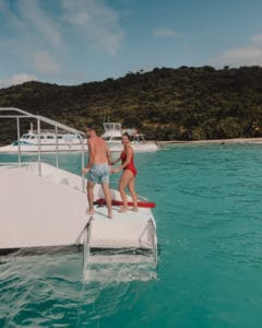 couple standing on edge of catamaran