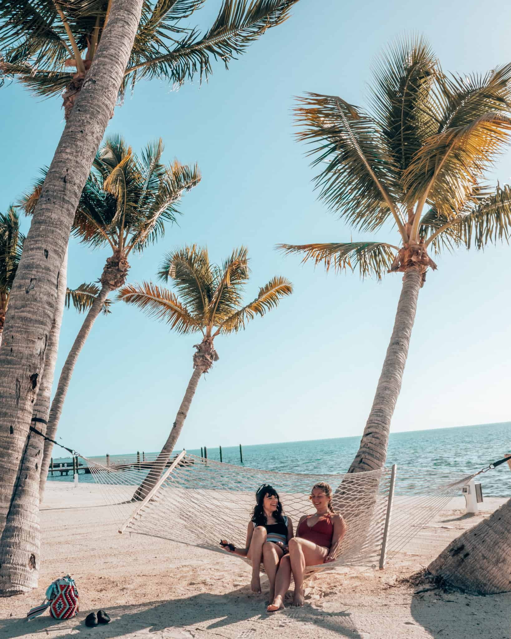 2 girls in a hammock hanging on palm trees