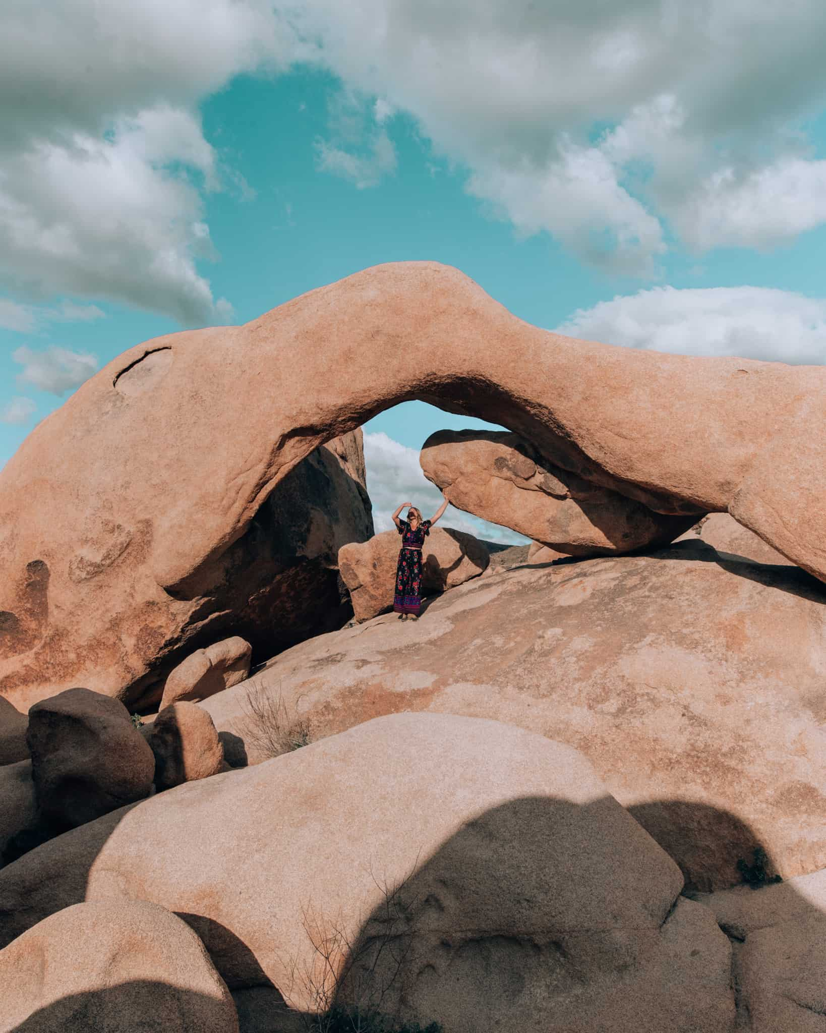girl standing in front of arch rock