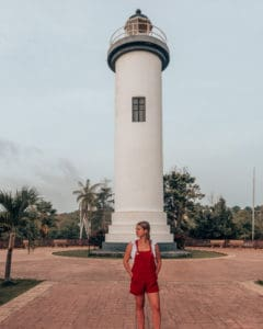 girl standing in front of lighhouse