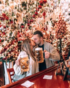 couple standing in restaurant with Christmas decor