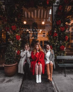 3 girls sitting on a bench outside of a boutique shop