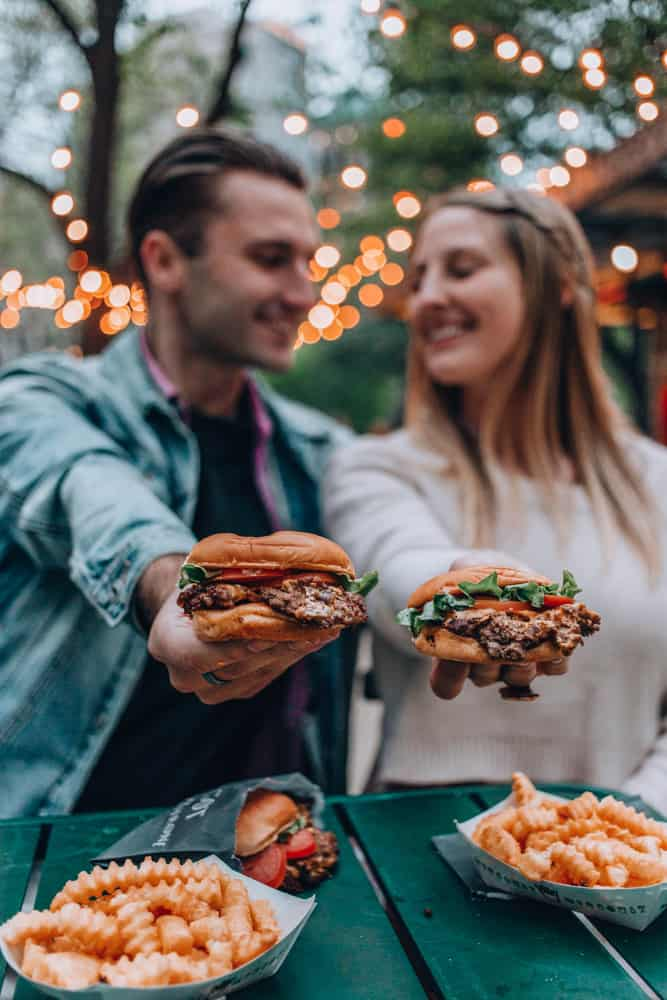 a couple holding up burgers