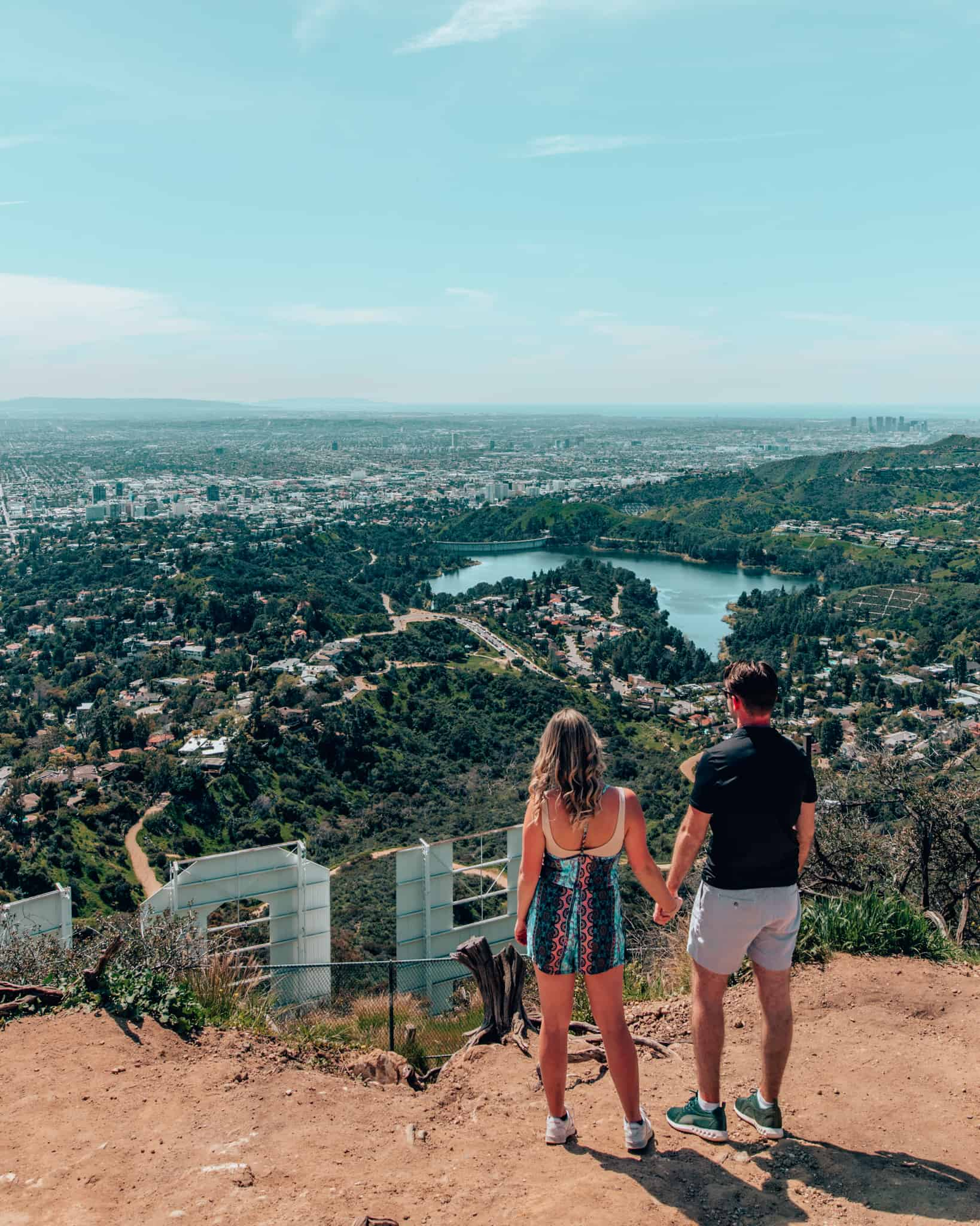 Couple standing behind the Hollywood Sign