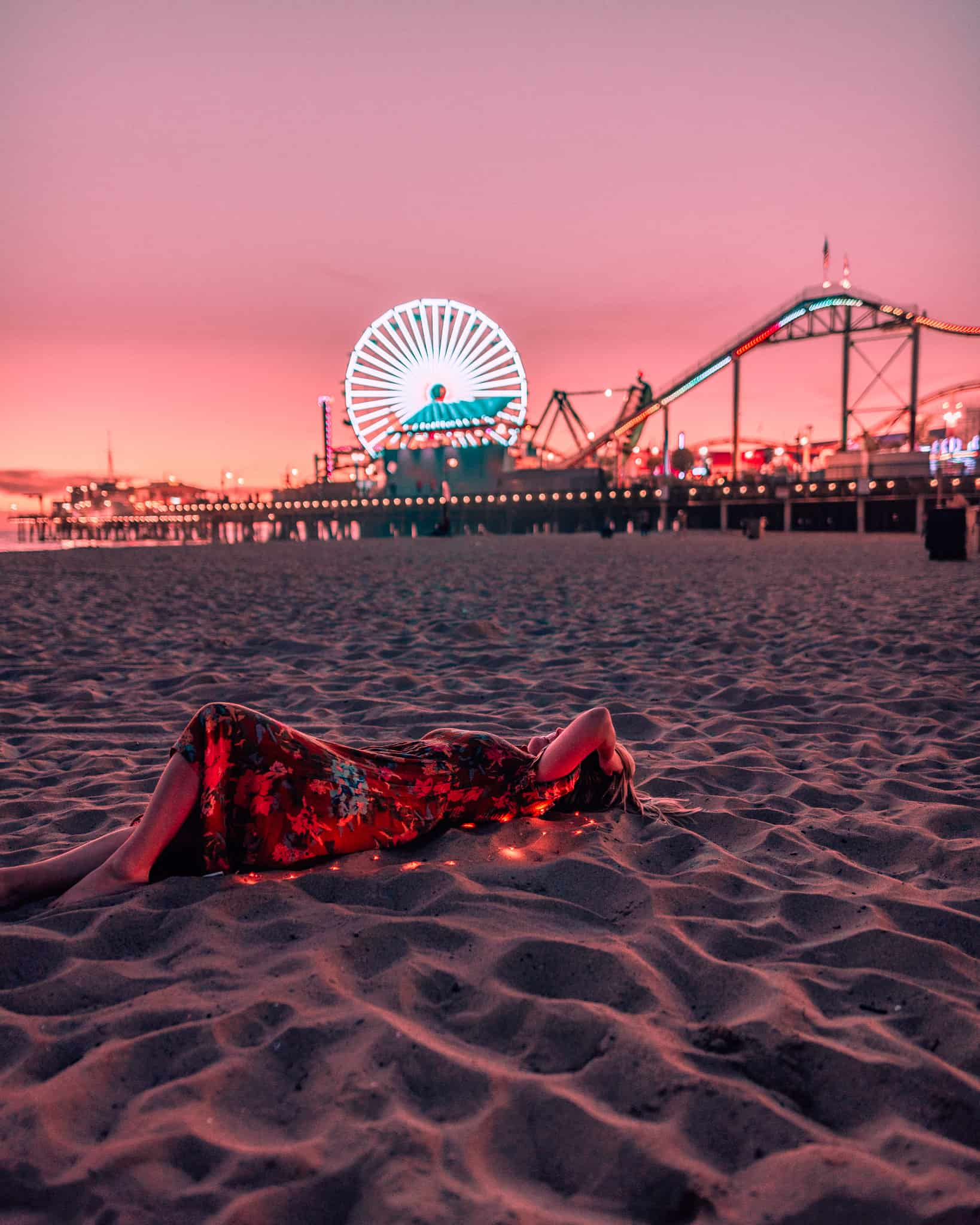 girl laying on beach in front of Santa Monica Pier