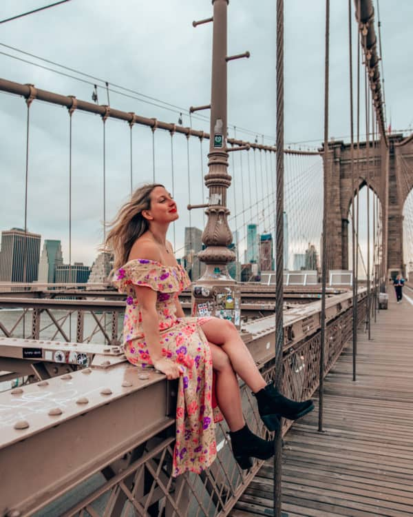 girl sitting on ledge at brooklyn bridge