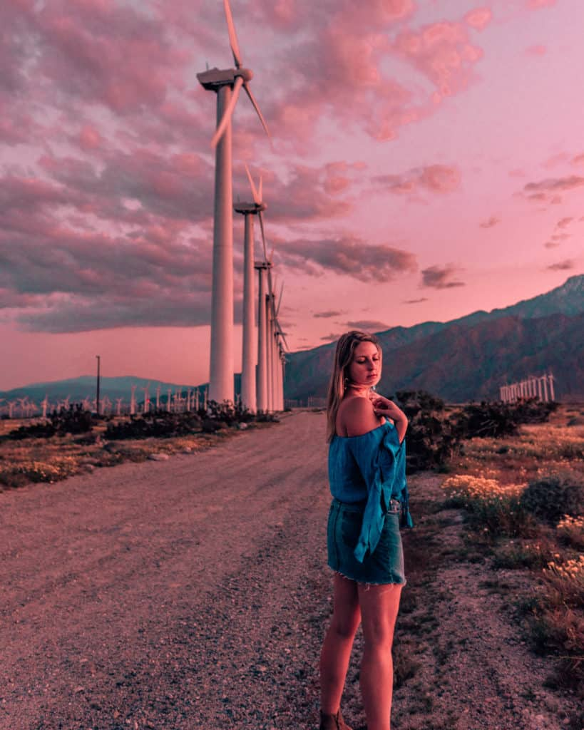 girl standing in front of windmills at sunset