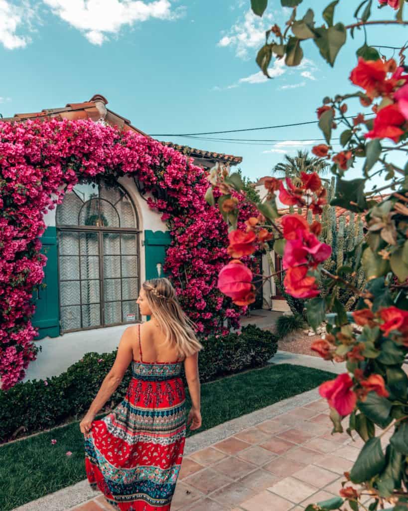 Girl standing next to pink rose bush