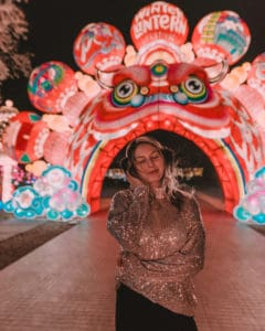 girl standing in front of an asian dragon lantern