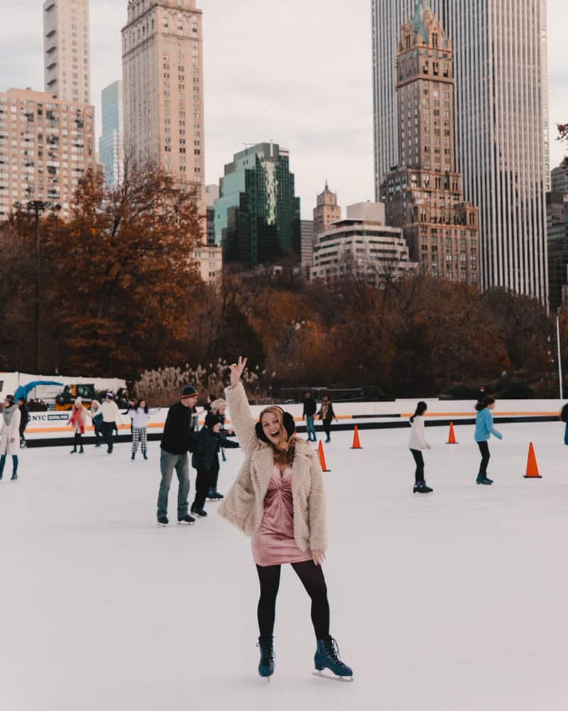 girl standing on skating rink holding up peace sign